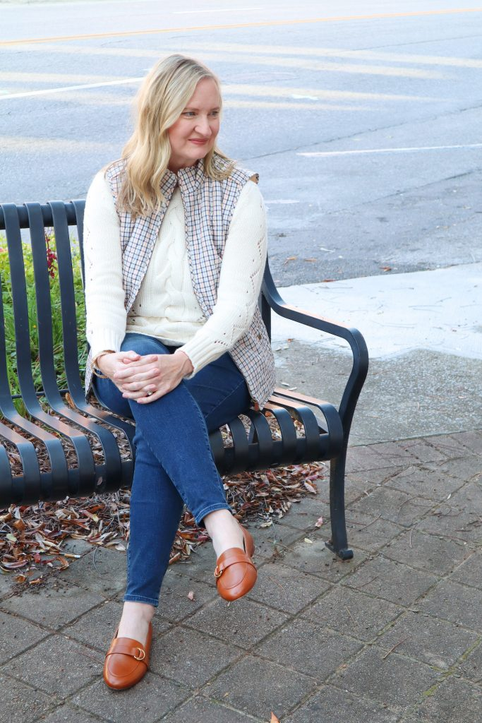 Classy Yet Trendy Wearing Talbots Cableknit Sweater Jeggings Diamond Quilted Vest Loafers Gold Bangle Earrings Bench